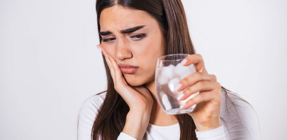 Young woman with sensitive teeth holding a glass of cold water with ice
