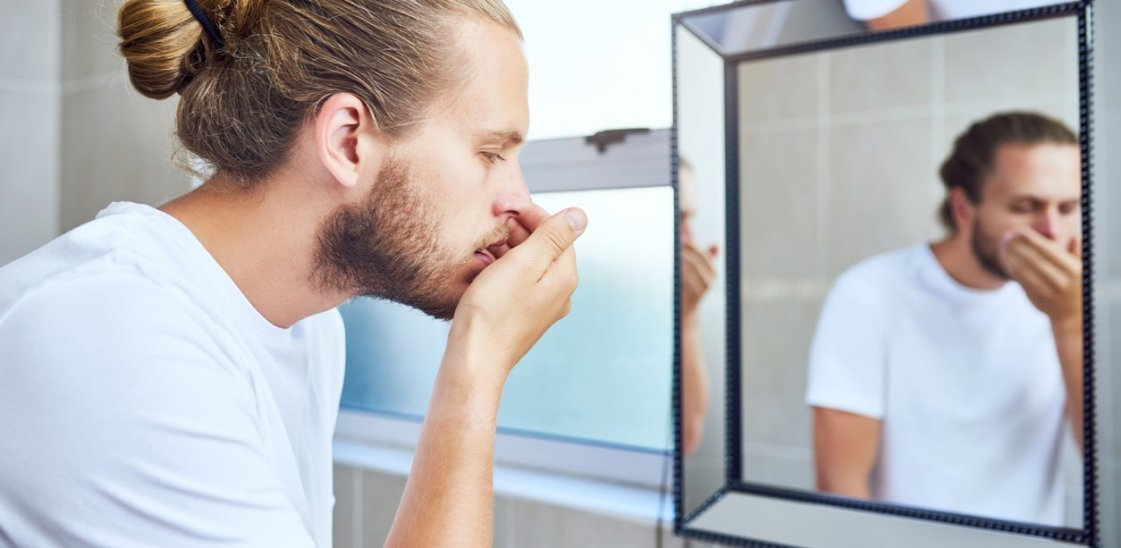 A man checking his breath for signs of halitosis
