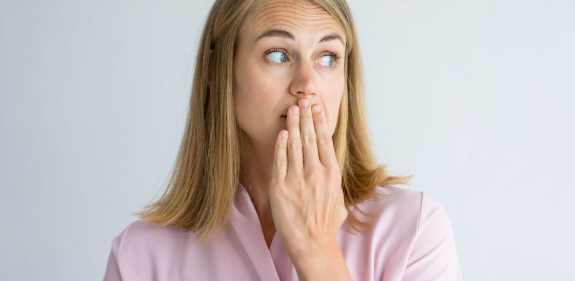 a woman with a hand over her mouth to cover bad breath
