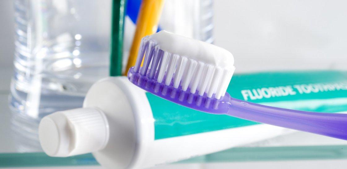 fluoride toothpaste next to a toothbrush