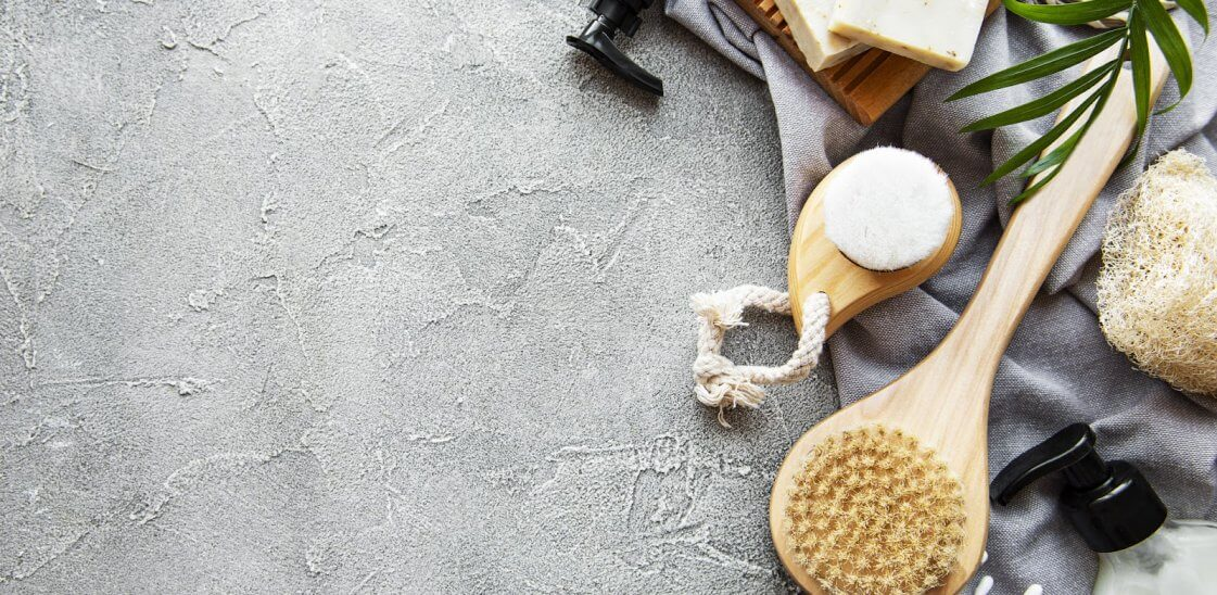 wooden eco-friendly products like cotton buds and toothbrushes laid out on a work surface.